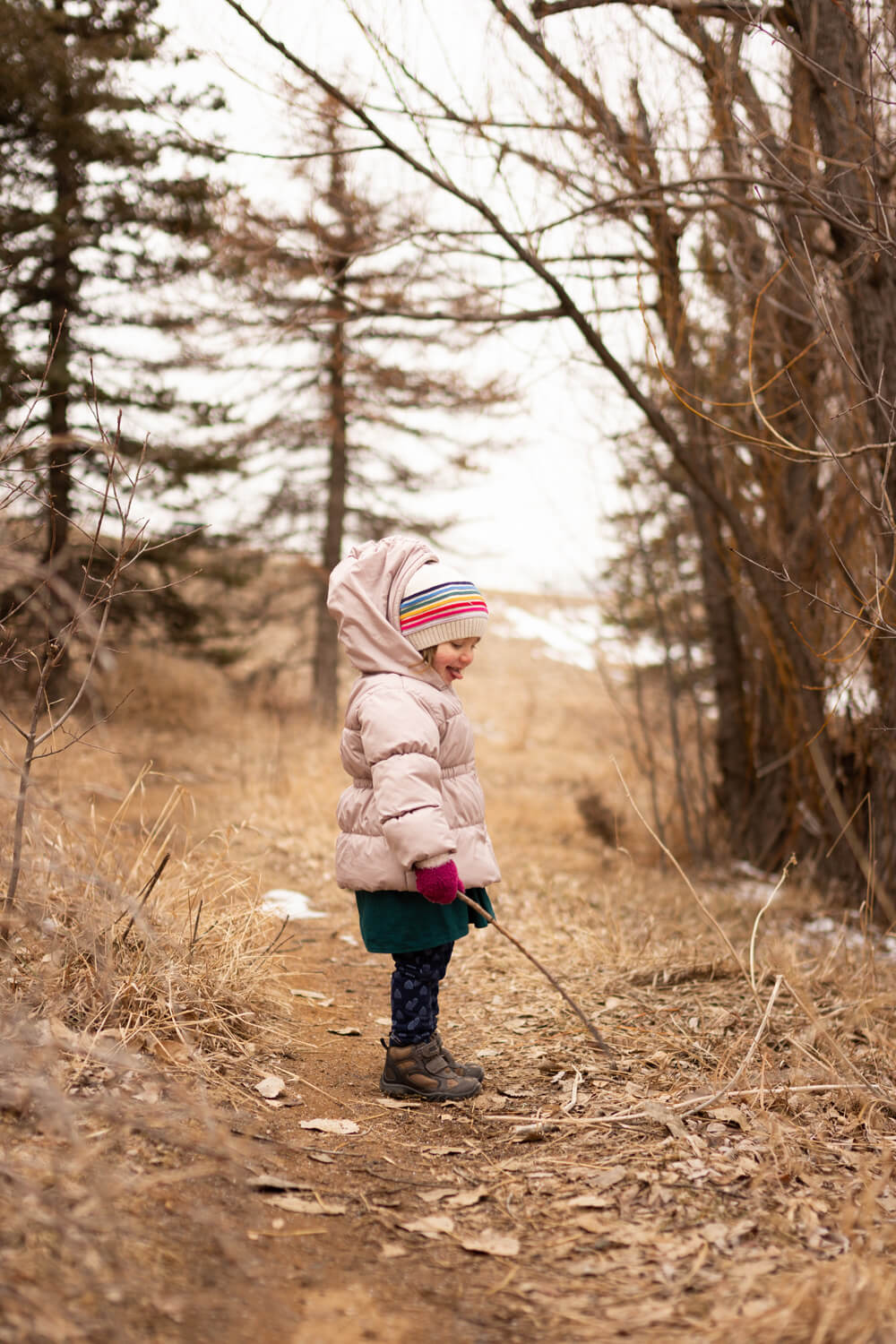 Portrait of a young girl wearing a rainbow striped hat picking up a stick