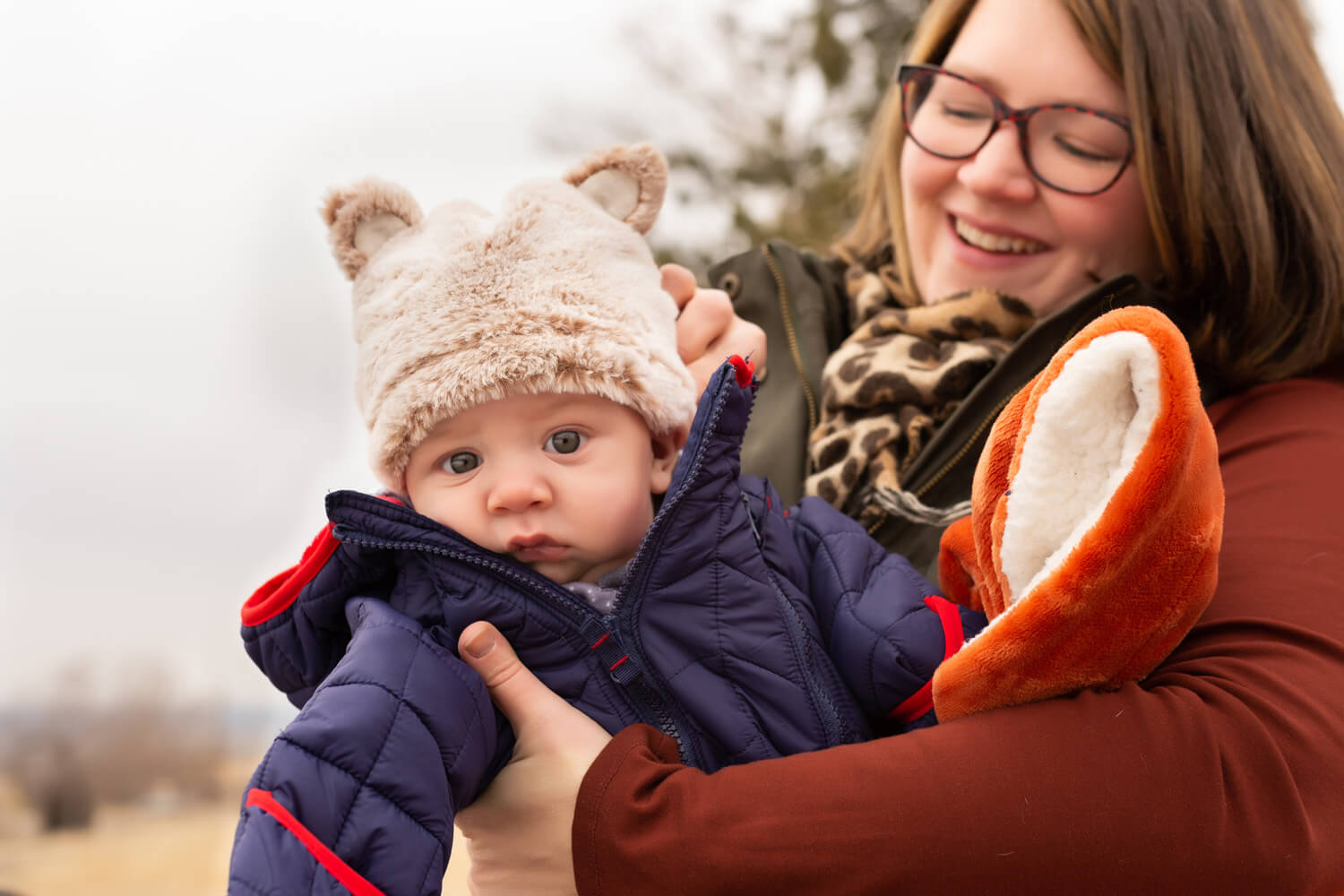 Portrait of a mama holding her baby as he wears a hat with fuzzy ears