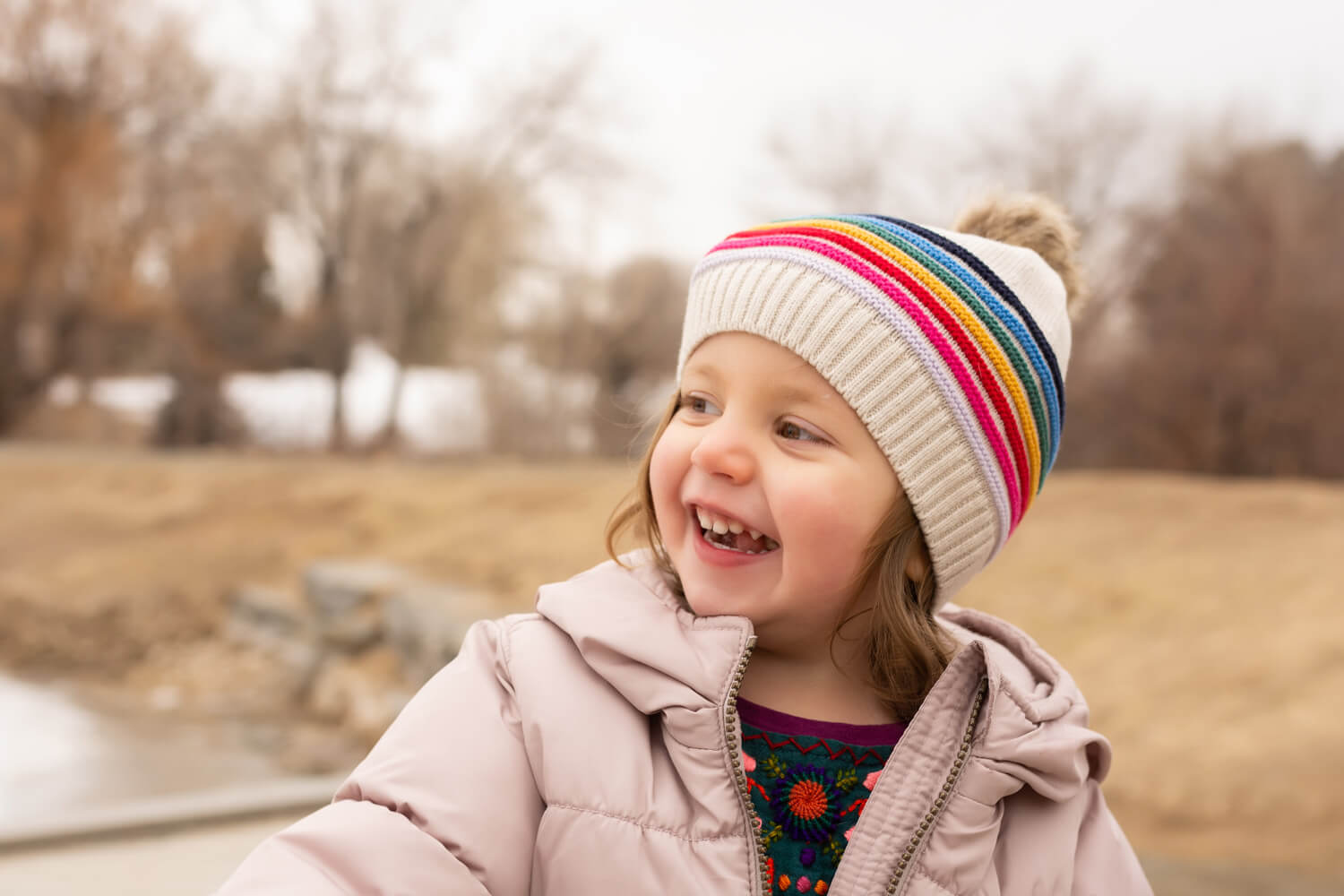 Portrait of a young girl wearing a rainbow striped hat laughing