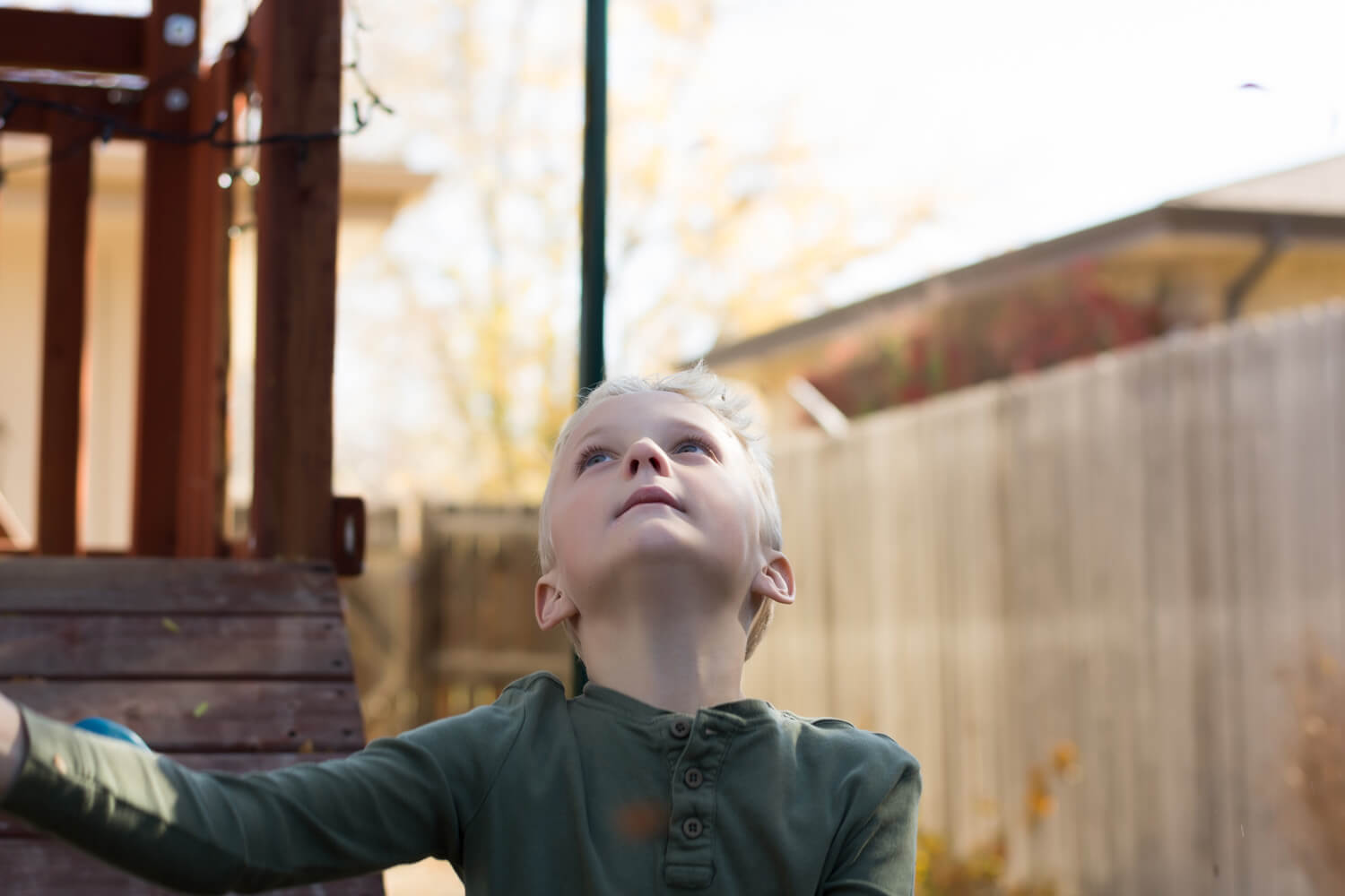 Portrait of a young boy looking up as he throws leaves