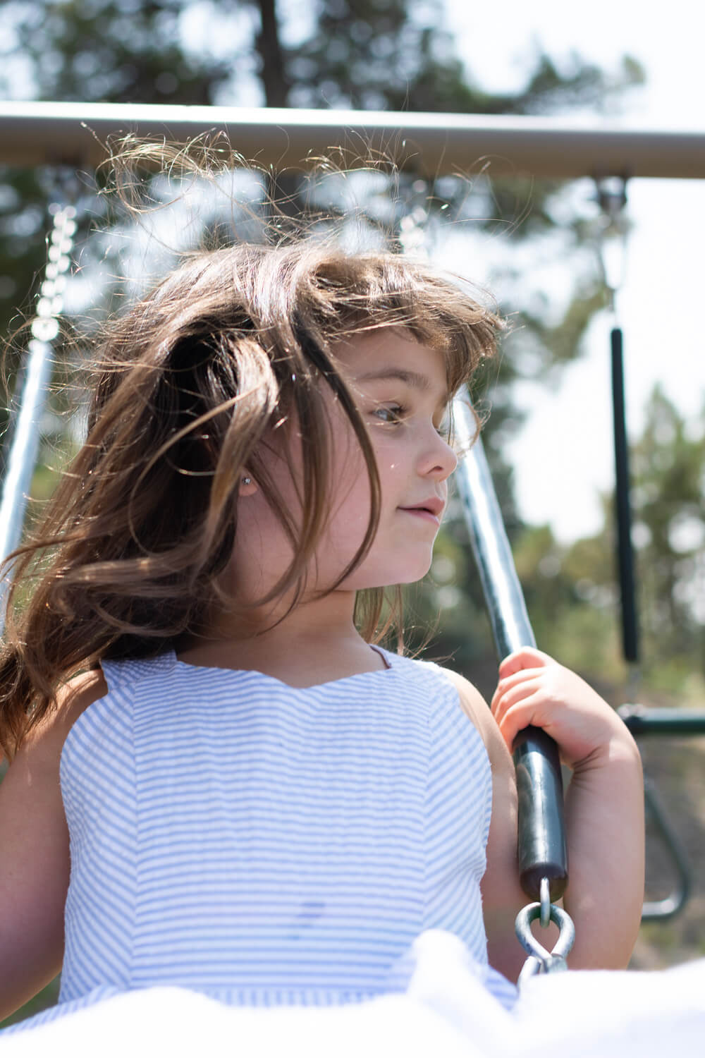 Portrait of a young girl swinging on a swing, her hair is flying in the breeze