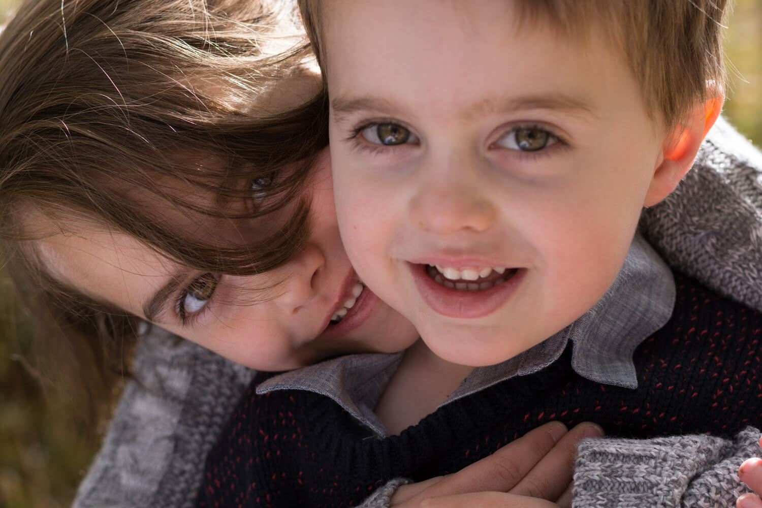 Portrait of a brother and sister hugging, both are looking into the camera